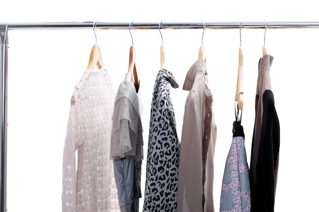 Vêtements pour femmes gris et beige sur des cintres en bois sur une grille sur fond blanc. femme d'affaires de placard