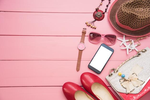 Vêtements pour femmes posés sur un sol en bois rose.