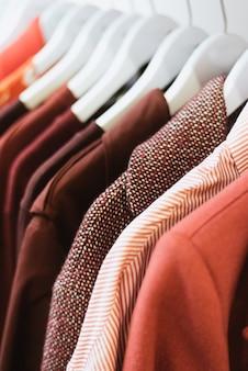 Des vêtements roses et bordeaux pour femmes sont suspendus dans le magasin.