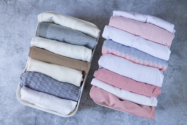 Vêtements soigneusement pliés dans des boîtes de rangement ouvertes