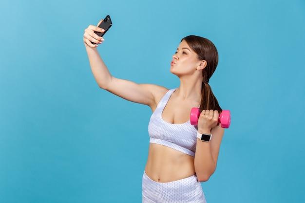 Vêtements de sport blancs pour femme posant devant la caméra de son smartphone, enregistrant une séance d'entraînement avec un didacticiel d'haltères
