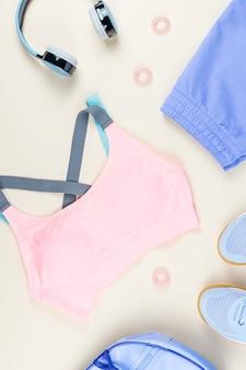 Vêtements de sport femme, baskets, écouteurs sur neutre.