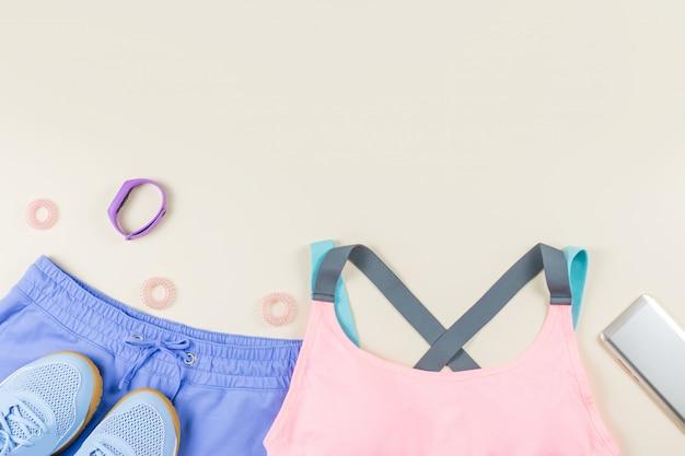 Vêtements de sport femme, baskets et tracker de fitness sur neutre