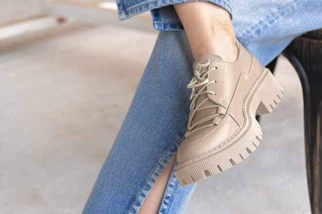 Vêtements de style de vie urbain, gros plan sur les baskets à la mode et les jeans en denim sur une adolescente. photo de concept de mode de rue