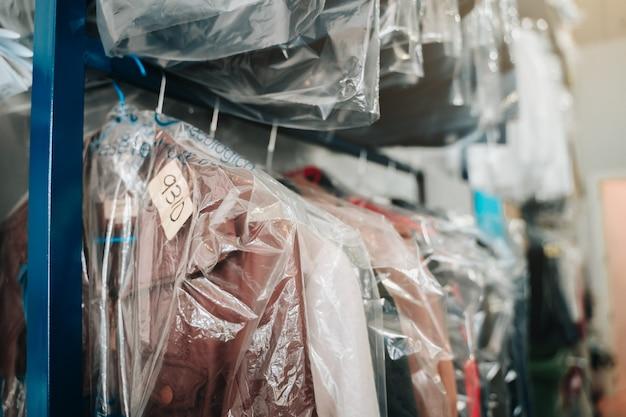 Vêtements suspendus sur des cintres dans un nettoyeur à sec