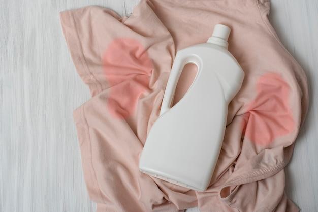 Des vêtements avec des taches et une bouteille de détergent. vue de dessus