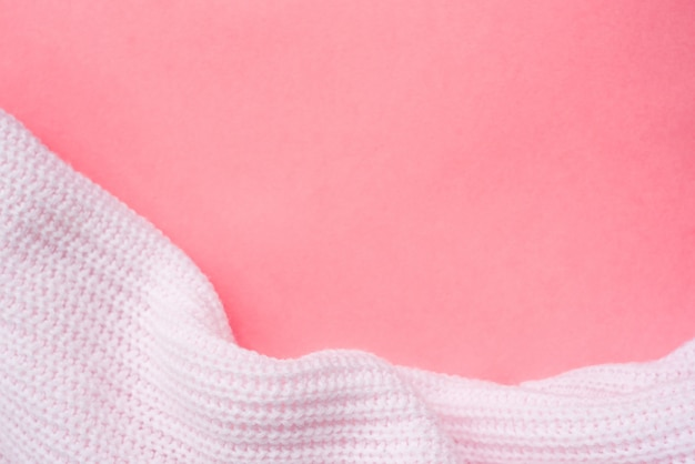 Vêtements tricotés roses sur fond de papier rose