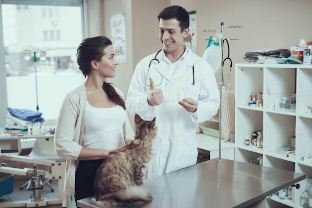 Le vétérinaire donne de bons médicaments au propriétaire du maine coon.