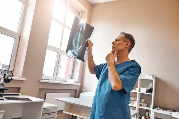 Vétérinaire masculin concentré en uniforme de travail regardant la radiographie de son patient
