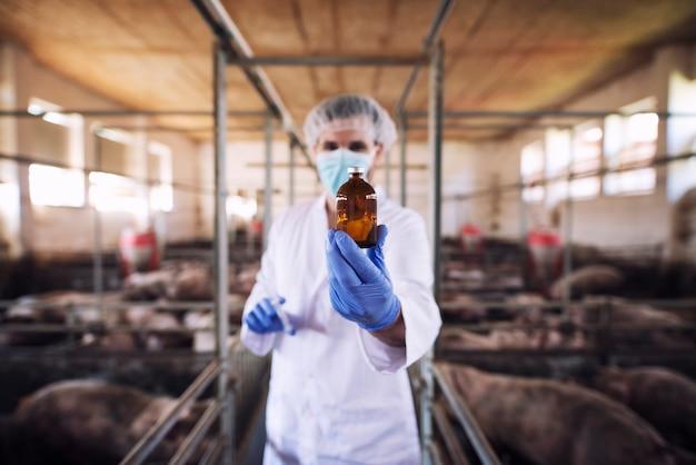 Vétérinaire en vêtements de protection tenant une bouteille avec des médicaments à la ferme porcine
