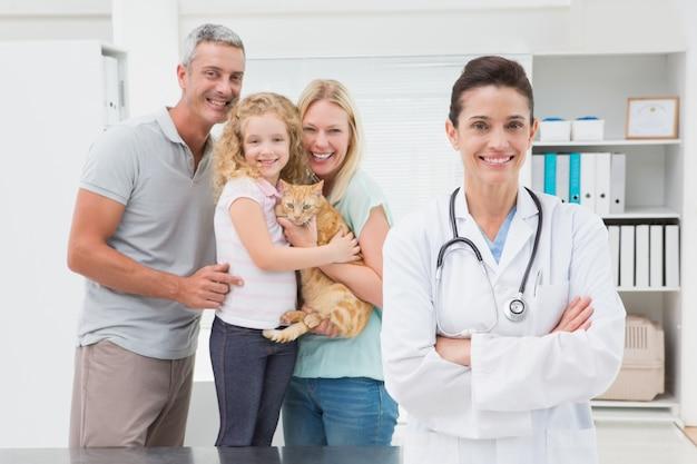 Vétérinaires et propriétaires de chat souriant à la caméra