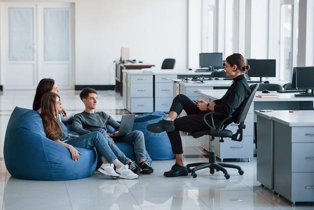 Veuillez m'écouter. groupe de jeunes en vêtements décontractés travaillant dans le bureau moderne