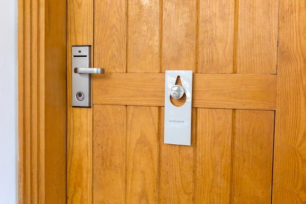 Veuillez ne pas déranger la signalisation sur la porte en bois fermée de la chambre d'hôtel