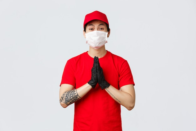Veuillez rester à la maison, nous livrons vos commandes. mignon livreur asiatique en bonnet rouge et t-shirt, portant un masque de protection et des gants, montre les mains en priant, mendiant, plaidant pour quelque chose