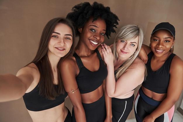 Veuillez sourire à la caméra. groupe de femmes multiethniques debout contre l'espace brun