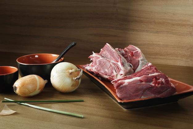Viande d'agneau crue fraîche dans une assiette sur la table. fond sombre.