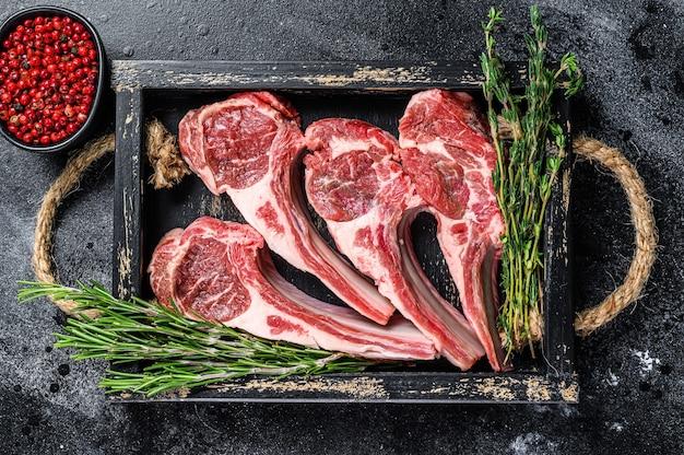 La viande d'agneau crue hache les steaks dans un plateau en bois. fond noir. vue de dessus.
