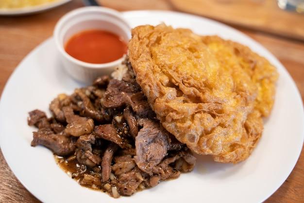 Viande d'agneau frite à l'ail sur du riz chaud et un œuf à l'omelette