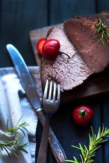 Viande au four au romarin et au poivron rouge. steak. du boeuf. dîner pour les hommes. photo sombre. fond noir. planche de bois.