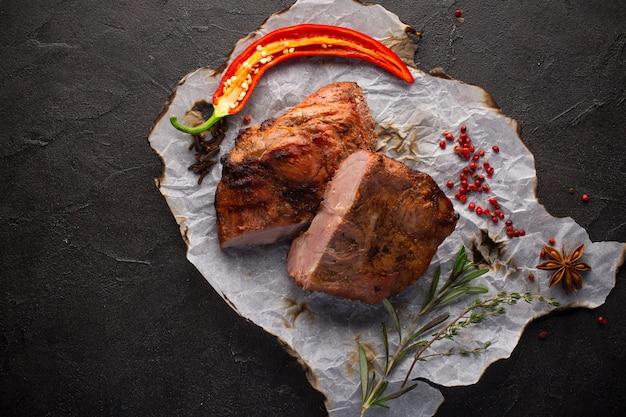 Viande au four avec des épices sur fond noir