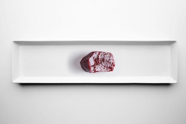 Viande de baleine de luxe cru isolée sur plaque blanche