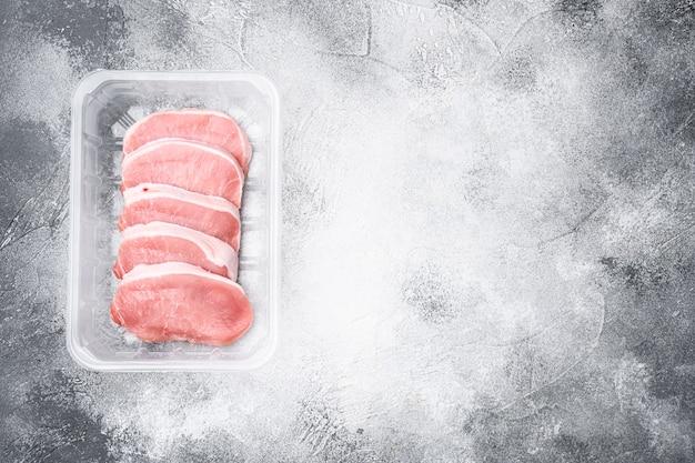Viande biologique crue. steaks de porc, filets pour griller, cuire ou frire, dans un récipient en plastique, sur fond de table en pierre grise, vue de dessus à plat, avec espace de copie pour le texte