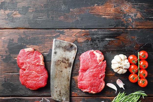Viande biologique de rumsteck coupée, steak de boeuf marbré cru, avec vieux couperet de boucher et assaisonnements sur une table rustique en bois foncé, vue de dessus avec un espace pour le texte.