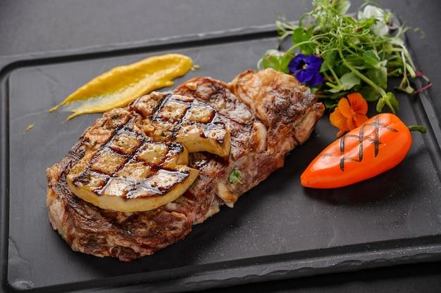 Viande de boeuf aux légumes sur pierre noire, cuite