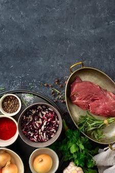 Viande de boeuf crue avec des ingrédients pour la cuisson d'aliments sains. viande de boeuf non cuite avec herbes, épices et haricots vue de dessus