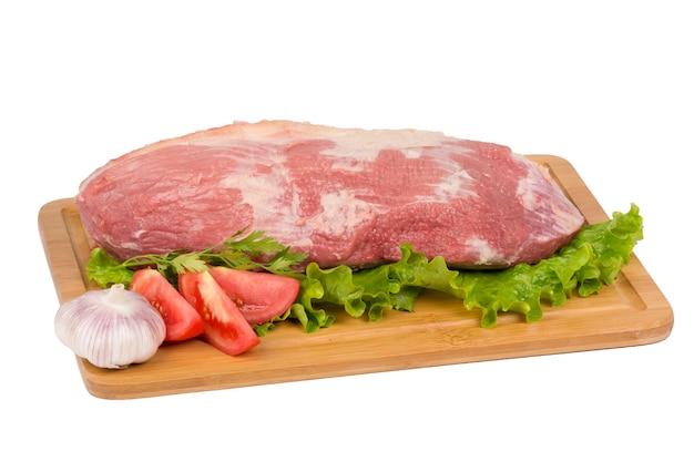 Viande de boeuf crue sur une planche à découper sur fond blanc.