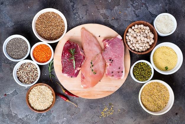 Viande de boeuf crue et poitrine de poulet avec des céréales dans un bol
