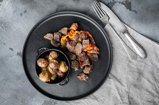 La viande de boeuf cuit avec des pommes de terre, des carottes et des épices, vue de dessus à plat