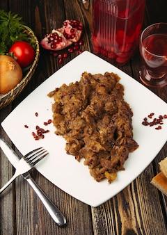Viande de bœuf épicée cuite avec des légumes dans une assiette blanche.