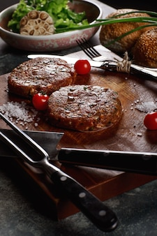 Viande de boeuf haché cru escalopes de steak burger avec des ingrédients sur le plateau