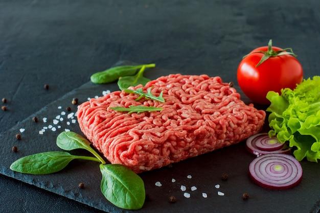 Viande de boeuf hachée crue sur une ardoise avec des feuilles et des épices.