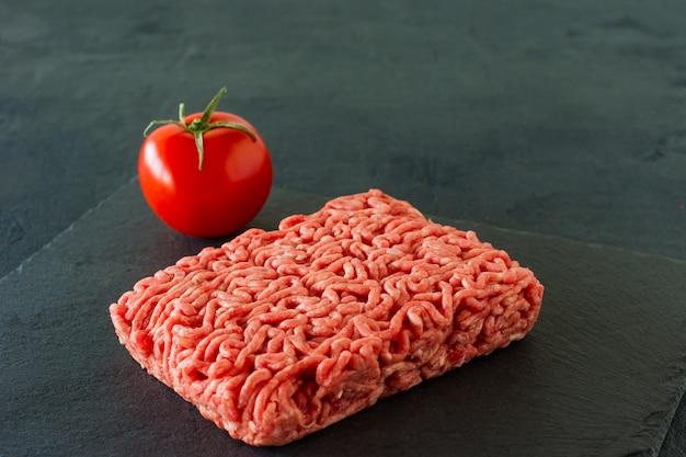 Viande de boeuf hachée crue sur une ardoise à la tomate.