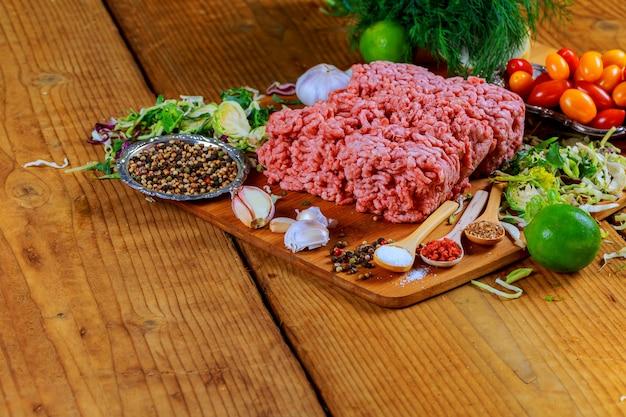 Viande de boeuf hachée crue côtelettes de bifteck avec assaisonnement, tomates,