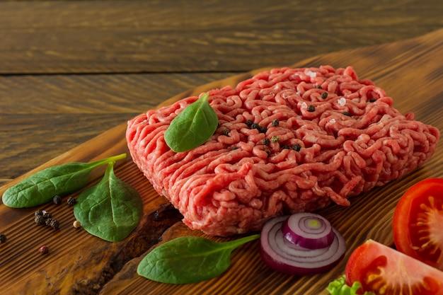 Viande de boeuf hachée crue sur une planche à découper en bois avec des légumes et des épices. concept de cuisine et d'alimentation saine.