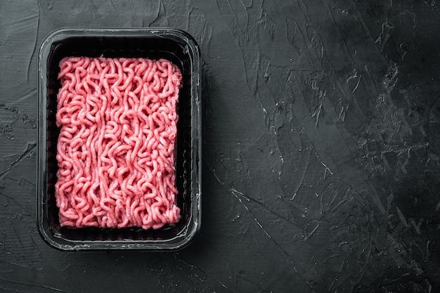 Viande de bœuf hachée dans un plateau en plastique, sur pierre noire