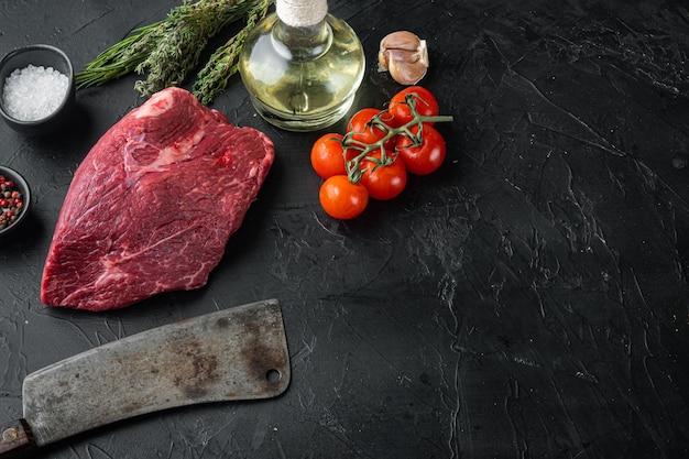 Viande de boeuf ronde crue sertie d'un vieux couteau de couperet de boucher, sur fond noir
