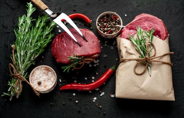 Viande de boucherie, deux steaks avec des ingrédients. deux morceaux de boeuf sur béton noir