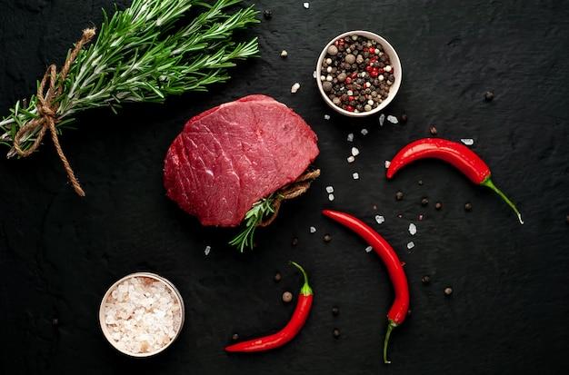 Viande de boucherie, steak avec ingrédients. un morceau de boeuf sur du béton noir