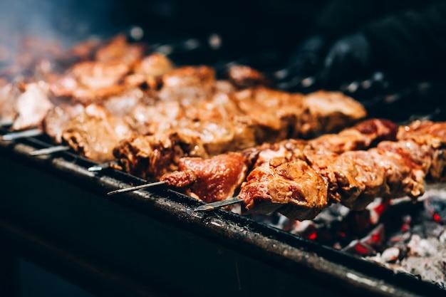 Viande à la broche. gril de porc. barbecue fumant dans la rue. cuisson du poulet shashlik. charbons brûlants.