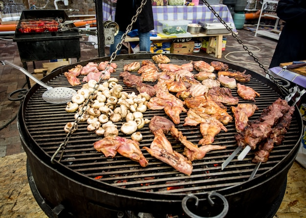 Viande et champignons cuisant sur un grand barbecue dans une cuisine extérieure