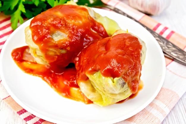 Viande de chou farcie dans des feuilles de chou avec sauce tomate dans l'assiette sur une serviette, persil et ail sur fond de planche de bois pâle