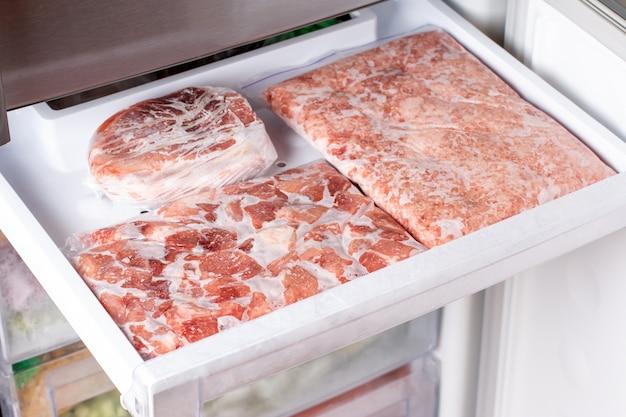 Viande congelée dans un emballage en plastique au congélateur. des surgelés