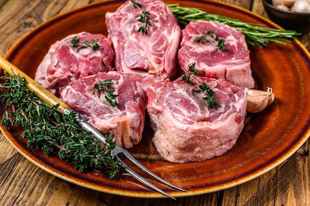 Viande de cou d'agneau de mouton sur une assiette rustique avec du thym et du romarin sur table en bois. vue de dessus.