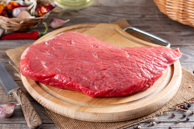 Viande crue, boeuf cru sur une planche à découper sur une table