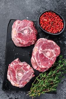 Viande crue de cou d'agneau sur une planche de marbre. fond noir. vue de dessus.