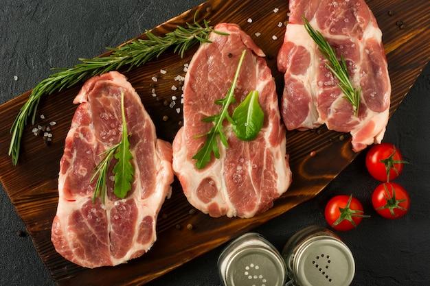 Viande crue de cou de porc pour des steaks hachés frais sur une planche à découper en bois. vue de dessus.